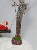 Santa Swinging On Bench Between Lit Trees Figurine - 20cm